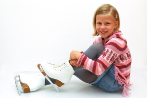 Cute girl sitting on ice skates